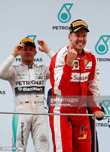 Sebastian Vettel of Germany and Ferrari celebrates on the podium next to Nico Rosberg of Germany and Mercedes GP after winning the Malaysia Formula...