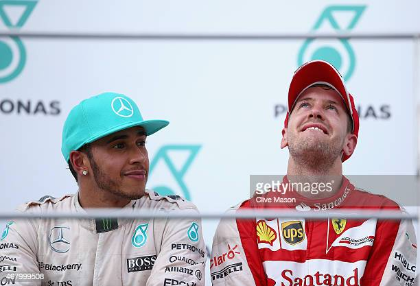 Sebastian Vettel of Germany and Ferrari celebrates on the podium next to Lewis Hamilton of Great Britain and Mercedes GP after winning the Malaysia...