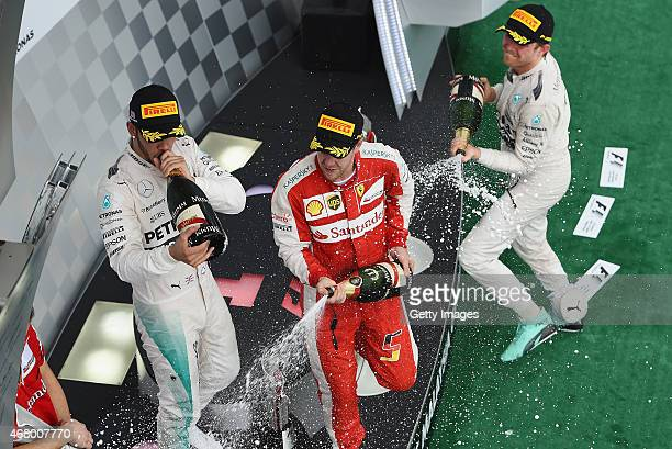 Sebastian Vettel of Germany and Ferrari celebrates on the podium next to Lewis Hamilton of Great Britain and Mercedes GP and Nico Rosberg of Germany...