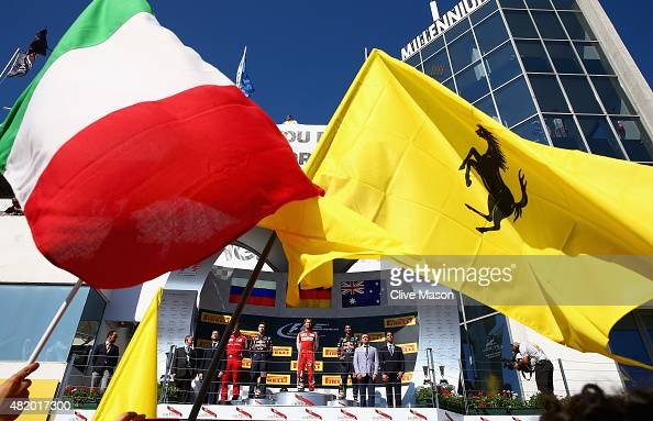 Sebastian Vettel of Germany and Ferrari celebrates on the podium next to Daniel Ricciardo of Australia and Infiniti Red Bull Racing Daniil Kvyat of...