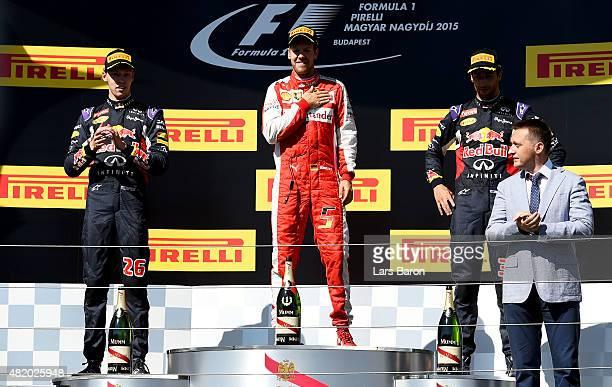 Sebastian Vettel of Germany and Ferrari celebrates on the podium next to Daniel Ricciardo of Australia and Infiniti Red Bull Racing and Daniil Kvyat...