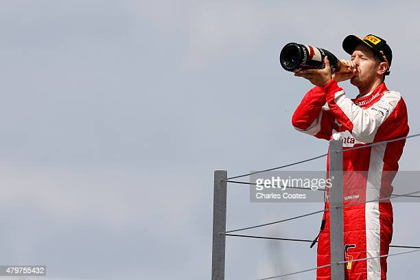 Sebastian Vettel of Germany and Ferrari celebrates on the podium after finishing third in the Formula One Grand Prix of Great Britain at Silverstone...