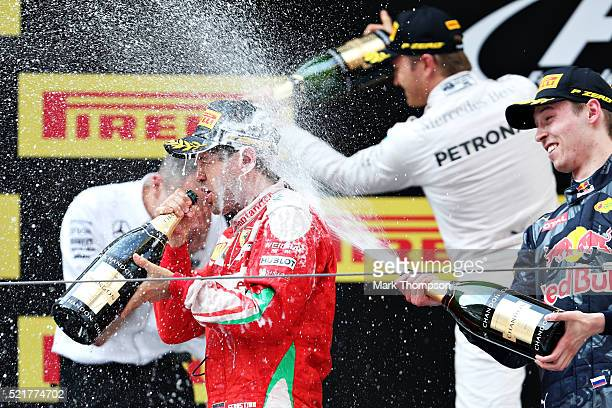 Sebastian Vettel of Germany and Ferrari celebrates with Daniil Kvyat of Russia and Red Bull Racing on the podium during the Formula One Grand Prix of...
