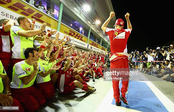 Sebastian Vettel of Germany and Ferrari celebrates with his team including Kimi Raikkonen of Finland and Ferrari and Ferrari Team Principal Maurizio...