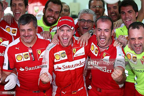 Sebastian Vettel of Germany and Ferrari celebrates with members of his team after winning the Malaysia Formula One Grand Prix at Sepang Circuit on...
