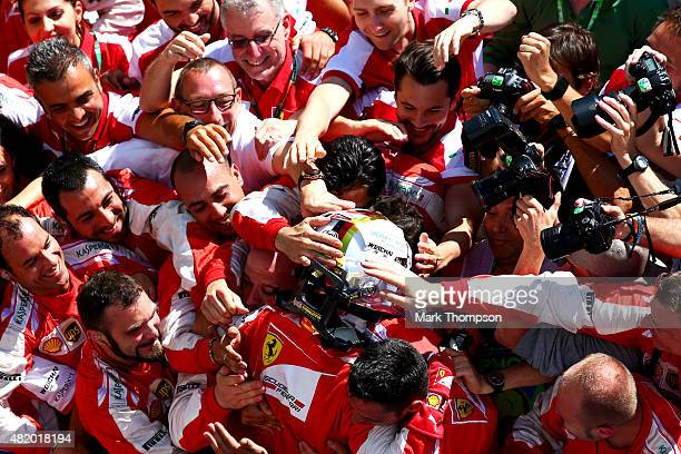 Sebastian Vettel of Germany and Ferrari celebrates with the team in Parc Ferme after winning the Formula One Grand Prix of Hungary at Hungaroring on...