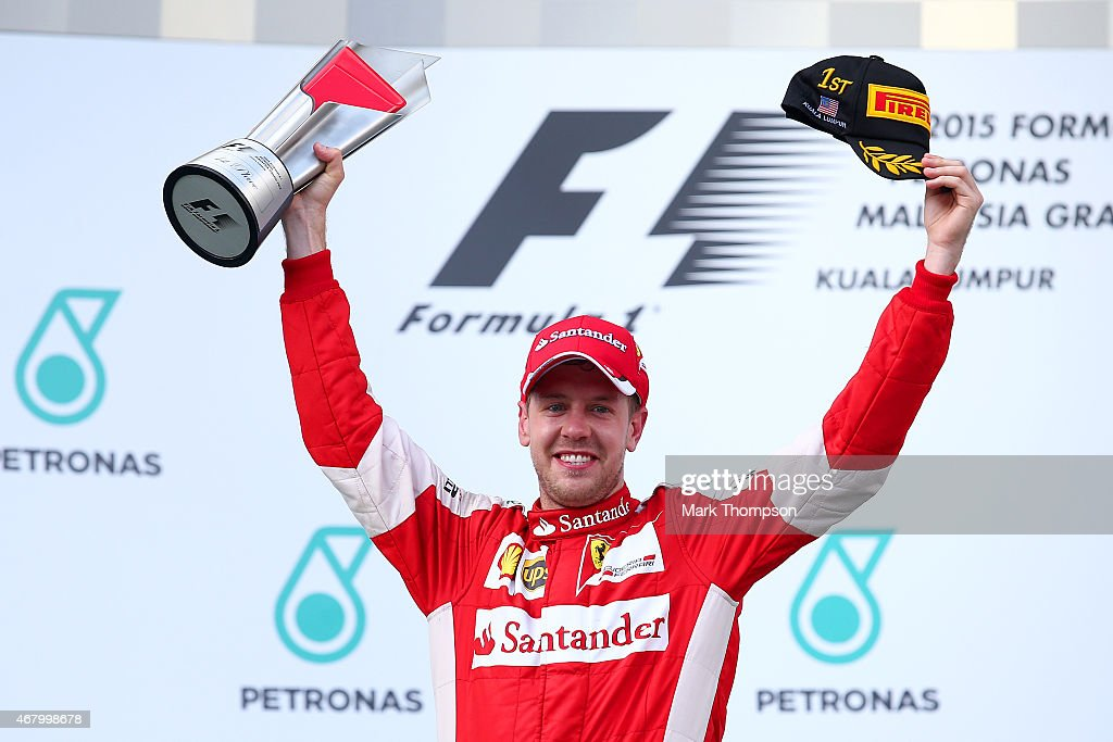Sebastian Vettel of Germany and Ferrari celebrates with the trophy on the podium after winning the Malaysia Formula One Grand Prix at Sepang Circuit on March 29, 2015 in Kuala Lumpur, Malaysia.
