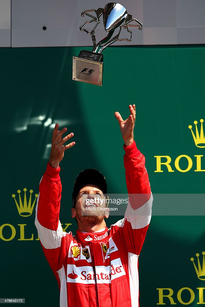 Sebastian Vettel of Germany and Ferrari celebrates with the trophy on the podium after finishing third in the Formula One Grand Prix of Great Britain at Silverstone Circuit on July 5, 2015 in Northampton, England.