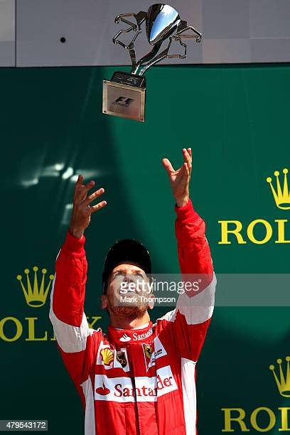 Sebastian Vettel of Germany and Ferrari celebrates with the trophy on the podium after finishing third in the Formula One Grand Prix of Great Britain...