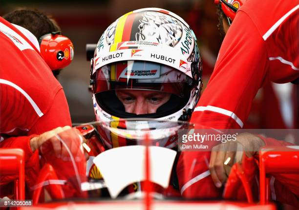 Sebastian Vettel of Germany and Ferrari climbs into his car fitted with the cockpit shield before practice for the Formula One Grand Prix of Great...