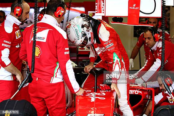 Sebastian Vettel of Germany and Ferrari climbs into his car in the garage with the halo fitted during practice for the Formula One Grand Prix of...