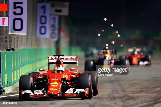Sebastian Vettel of Germany and Ferrari drives ahead of Daniel Ricciardo of Australia and Infiniti Red Bull Racing and Kimi Raikkonen of Finland and...