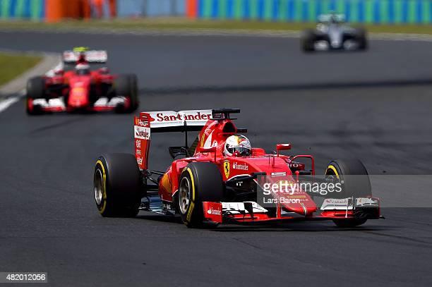 Sebastian Vettel of Germany and Ferrari drives ahead of Kimi Raikkonen of Finland and Ferrari and Nico Rosberg of Germany and Mercedes GP during the...