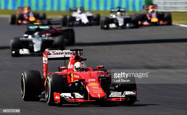 Sebastian Vettel of Germany and Ferrari drives ahead of Nico Rosberg of Germany and Mercedes GP during the Formula One Grand Prix of Hungary at...