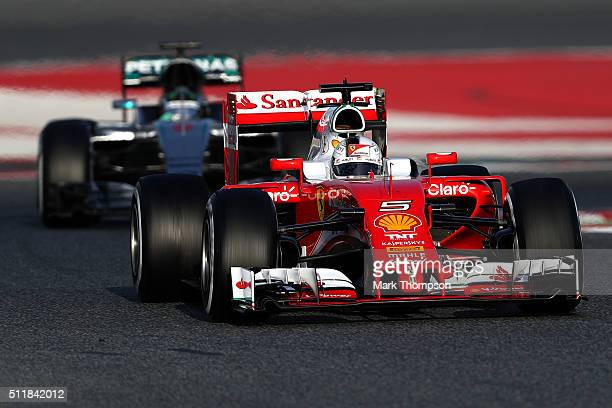 Sebastian Vettel of Germany and Ferrari drives ahead of Nico Rosberg of Germany and Mercedes GP during day two of F1 winter testing at Circuit de...