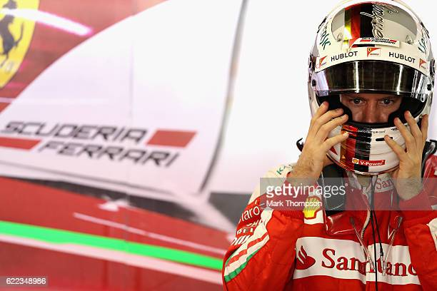 Sebastian Vettel of Germany and Ferrari gets ready in the garage during practice for the Formula One Grand Prix of Brazil at Autodromo Jose Carlos...