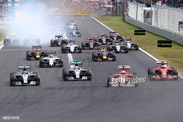 Sebastian Vettel of Germany and Ferrari leads Nico Rosberg of Germany and Mercedes GP Lewis Hamilton of Great Britain and Mercedes GP and Kimi...