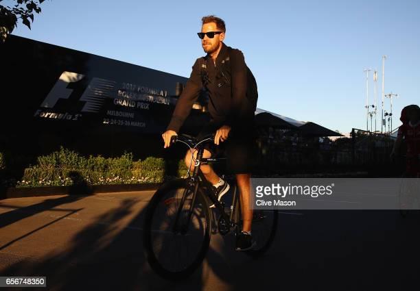 Sebastian Vettel of Germany and Ferrari leaves the circuit on his bike during previews to the Australian Formula One Grand Prix at Albert Park on...
