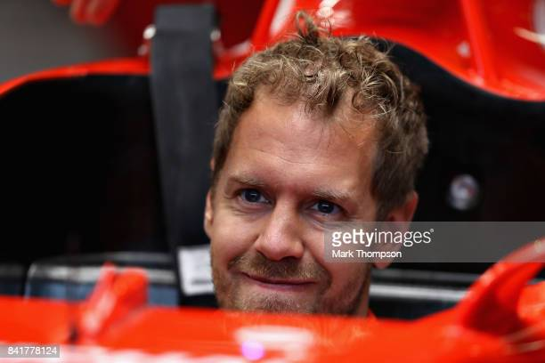 Sebastian Vettel of Germany and Ferrari looks on in the garage during a rain delayed final practice for the Formula One Grand Prix of Italy at...