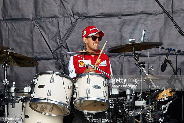Sebastian Vettel of Germany and Ferrari plays the drums on stage during a fan event after qualifying for the Formula One Grand Prix of Austria at Red...