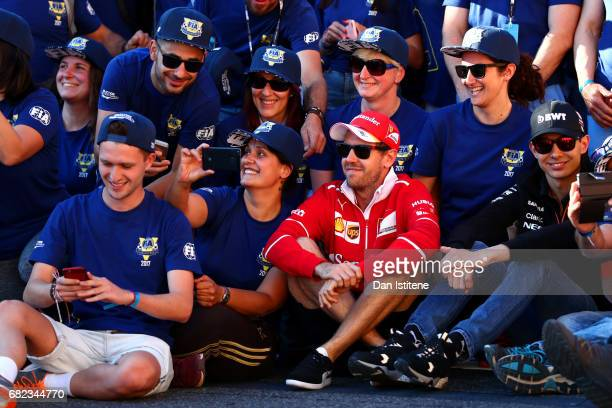 Sebastian Vettel of Germany and Ferrari poses with Spanish Grand Prix volunteers on the grid to mark the first FIA Volunteers' Day after practice for...