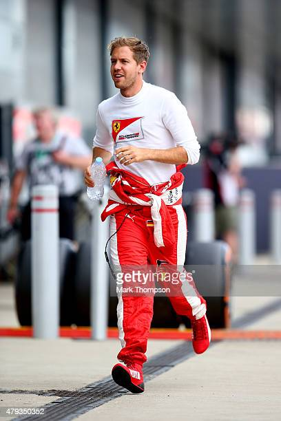 Sebastian Vettel of Germany and Ferrari runs in the paddock during practice for the Formula One Grand Prix of Great Britain at Silverstone Circuit on...