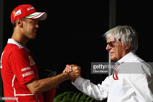 Sebastian Vettel of Germany and Ferrari shakes hands with Bernie Ecclestone Chairman Emeritus of the Formula One Group before the Bahrain Formula One...