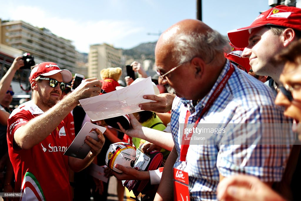 Sebastian Vettel of Germany and Ferrari signs autographs for fans during previews to the Monaco Formula One Grand Prix at Circuit de Monaco on May 27, 2016 in Monte-Carlo, Monaco.
