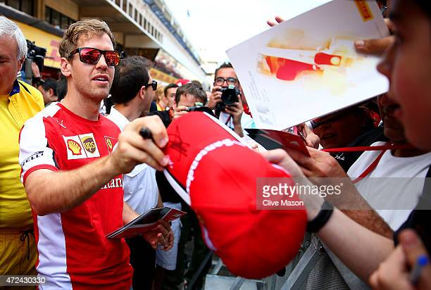 Sebastian Vettel of Germany and Ferrari signs his own cap for a fan in the pit lane during previews to the Spanish Formula One Grand Prix at Circuit...