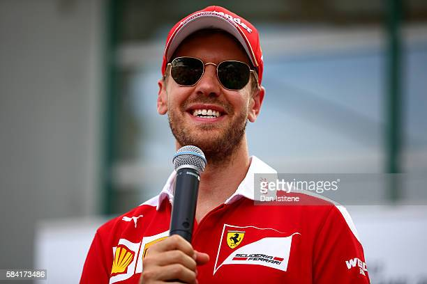 Sebastian Vettel of Germany and Ferrari talks to the crowd from the stage at the Shell fan quiz event during the Formula One Grand Prix of Germany at...