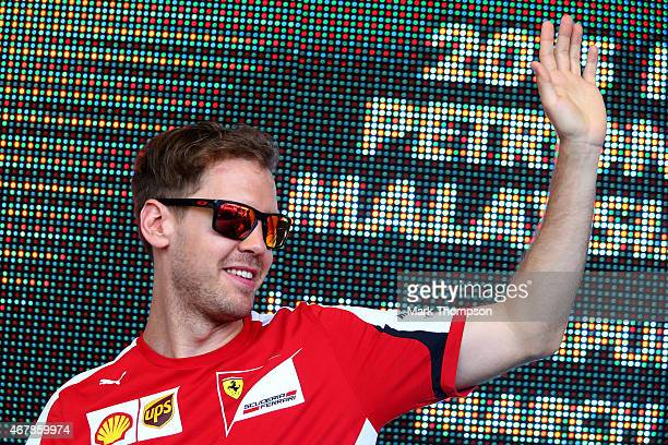 Sebastian Vettel of Germany and Ferrari waves to the crowd on stage at a fan forum before final practice for the Malaysia Formula One Grand Prix at...