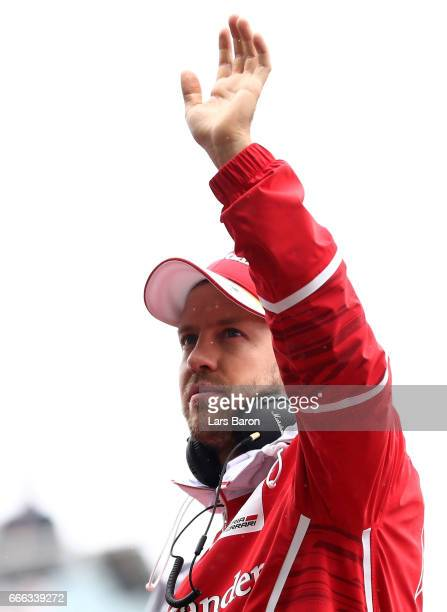Sebastian Vettel of Germany and Ferrari waves to the crowd on the drivers parade before the Formula One Grand Prix of China at Shanghai International...