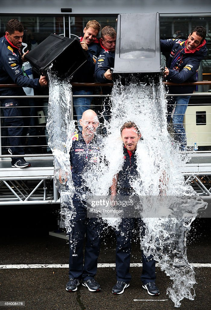 Sebastian Vettel of Germany and Infiniti Red Bull Racing and Daniel Ricciardo of Australia and Infiniti Red Bull Racing pour buckets of ice water over Infiniti Red Bull Racing Team Principal Christian Horner and Adrian Newey, the Infiniti Red Bull Racing Chief Technical Officer during an ice bucket challenge after qualifying ahead of the Belgian Grand Prix at Circuit de Spa-Francorchamps on August 23, 2014 in Spa, Belgium.