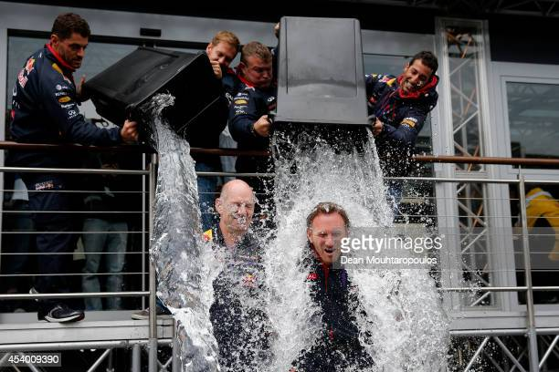 Sebastian Vettel of Germany and Infiniti Red Bull Racing and Daniel Ricciardo of Australia and Infiniti Red Bull Racing pour buckets of ice water...