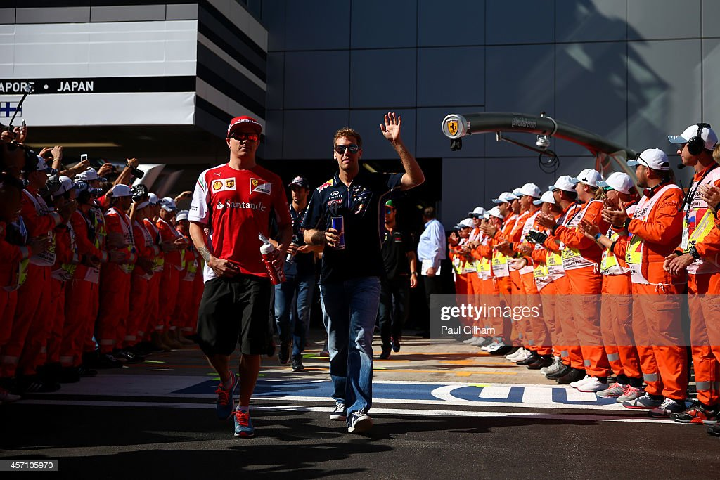 Sebastian Vettel of Germany and Infiniti Red Bull Racing and Kimi Raikkonen of Finland and Ferrari arrive for the drivers' parade before the Russian Formula One Grand Prix at Sochi Autodrom on October 12, 2014 in Sochi, Russia.