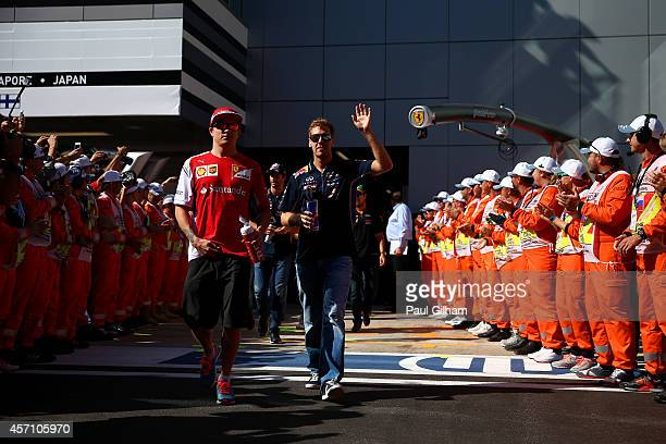 Sebastian Vettel of Germany and Infiniti Red Bull Racing and Kimi Raikkonen of Finland and Ferrari arrive for the drivers' parade before the Russian...