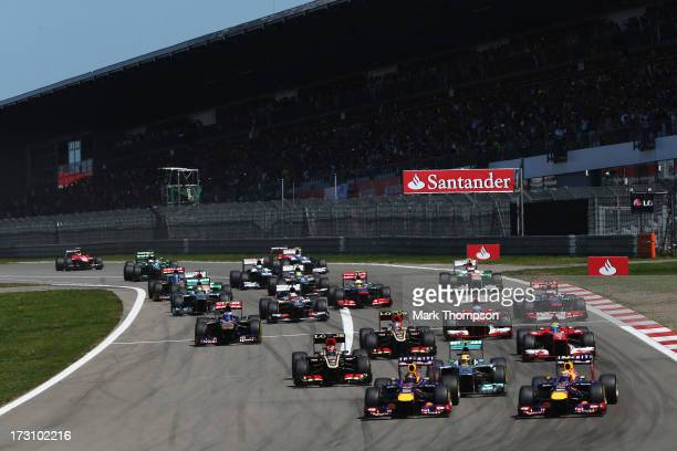 Sebastian Vettel of Germany and Infiniti Red Bull Racing and Mark Webber of Australia and Infiniti Red Bull Racing lead the field into the first...