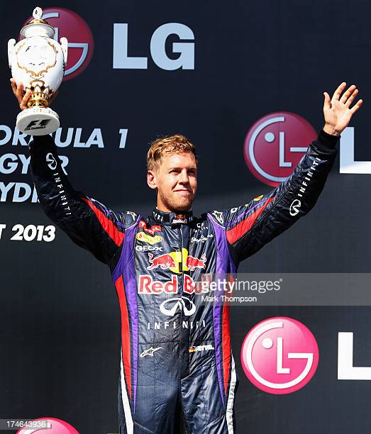 Sebastian Vettel of Germany and Infiniti Red Bull Racing celebrates on the podium after finishing third during the Hungarian Formula One Grand Prix...