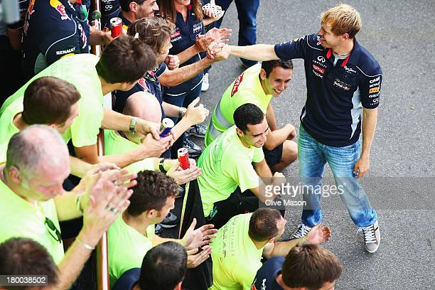 Sebastian Vettel of Germany and Infiniti Red Bull Racing celebrates with team mates in the paddock after winning the Italian Formula One Grand Prix...