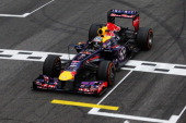 Sebastian Vettel of Germany and Infiniti Red Bull Racing celebrates as he crosses the finishing line to win the Brazilian Formula One Grand Prix at...
