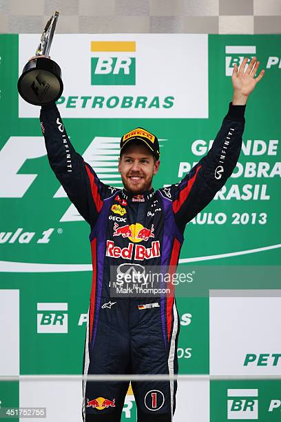 Sebastian Vettel of Germany and Infiniti Red Bull Racing celebrates on the podium after winning the Brazilian Formula One Grand Prix at Autodromo...