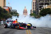 Sebastian Vettel of Germany and Infiniti Red Bull Racing drives along North Congress Avenue backdropped by the Texas Capitol building during previews...