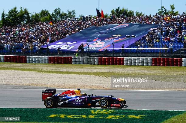 Sebastian Vettel of Germany and Infiniti Red Bull Racing drives past a giant banner supporting him during the German Grand Prix at the Nuerburgring...