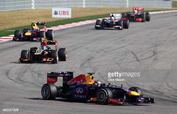 Sebastian Vettel of Germany and Infiniti Red Bull Racing leads from Romain Grosjean of France and Lotus and Mark Webber of Australia and Infiniti Red...