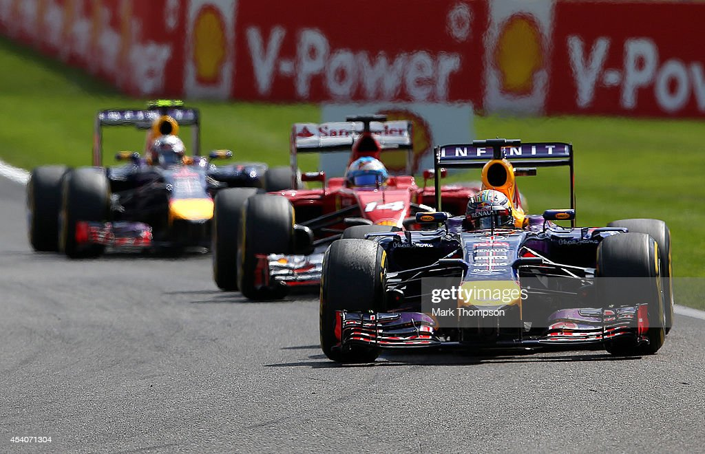 Sebastian Vettel of Germany and Infiniti Red Bull Racing leads Fernando Alonso of Spain and Ferrari and Daniel Ricciardo of Australia and Infiniti Red Bull Racing into turn one during the Belgian Grand Prix at Circuit de Spa-Francorchamps on August 24, 2014 in Spa, Belgium.