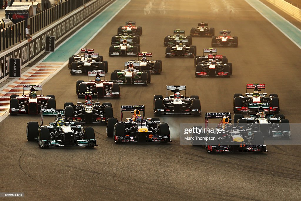 Sebastian Vettel (front right) of Germany and Infiniti Red Bull Racing leads the field into the first corner at the start of the Abu Dhabi Formula One Grand Prix at the Yas Marina Circuit on November 3, 2013 in Abu Dhabi, United Arab Emirates.