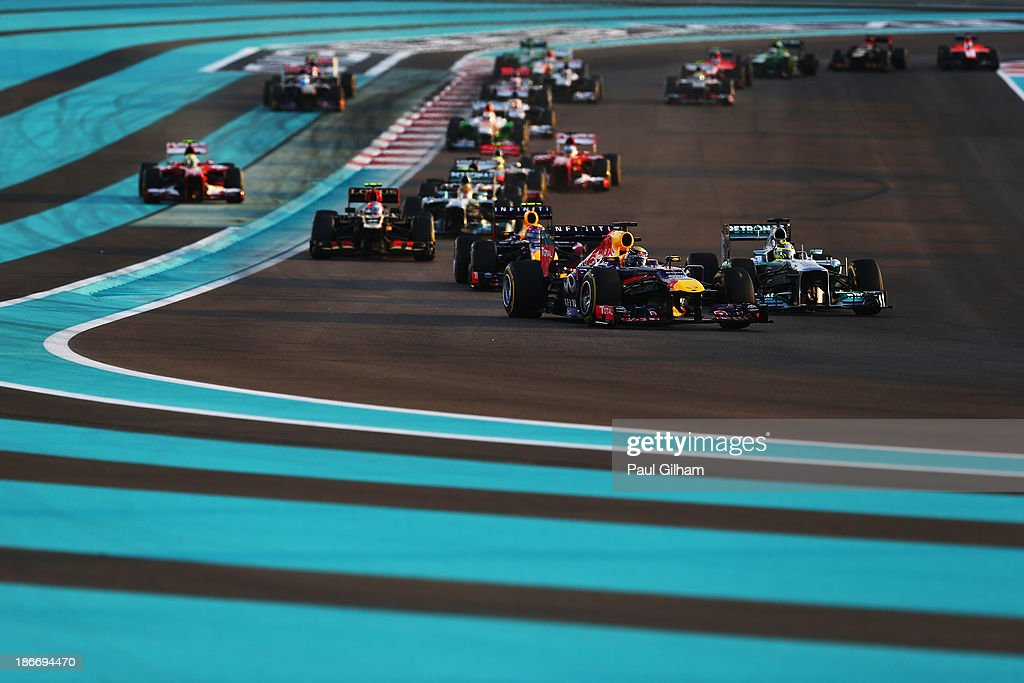 Sebastian Vettel (front left) of Germany and Infiniti Red Bull Racing leads the field through turns one and two at the start of the Abu Dhabi Formula One Grand Prix at the Yas Marina Circuit on November 3, 2013 in Abu Dhabi, United Arab Emirates.