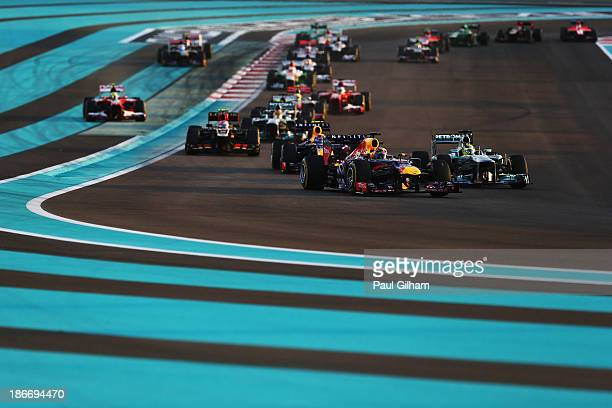 Sebastian Vettel of Germany and Infiniti Red Bull Racing leads the field through turns one and two at the start of the Abu Dhabi Formula One Grand...