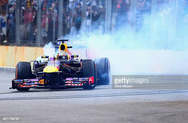 Sebastian Vettel of Germany and Infiniti Red Bull Racing performs donuts in his car after winning the Brazilian Formula One Grand Prix at Autodromo...