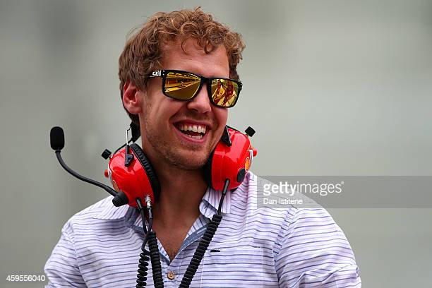 Sebastian Vettel of Germany and Infiniti Red Bull Racing smiles as he speaks with members of the Ferrari team on the pit wall during day one of...